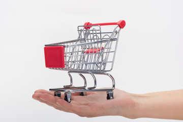 Hand holds empty grocery cart, white background