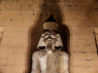 Granite statue of Ramses II at Luxor Temple illuminated at night