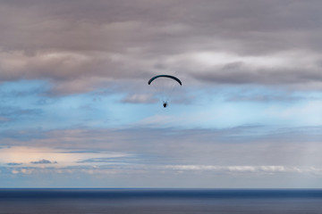 Scene of paraglider over the sea against cloudy blue sky at sunset