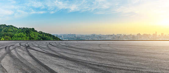 Panoramic city skyline and buildings with empty asphalt road at sunrise Fotomurales
