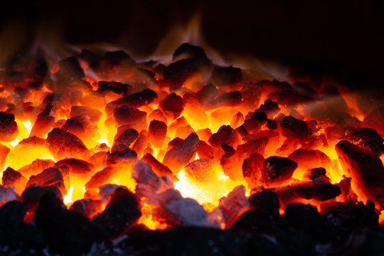 Abstract background of glowing coals in fireplace with fire flames. Burning flame background