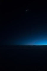 Night sky of dark blue color and strong clouds and very small moon silhouette at deep night