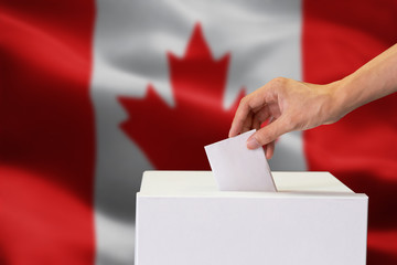 Close-up of human hand casting and inserting a vote and choosing and making a decision what he wants in polling box with Canada flag blended in background Fototapete