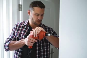 Male carpenter using drill machine