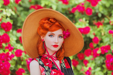 Trendy girl with retro hairstyle with red lips in rose print dress on summer garden. Spring blossom flower. Redhead model in trendy summer hat on blossom rose bush. Stylish hairstyle. Spring flower