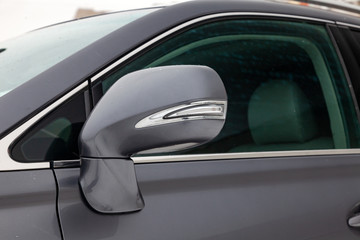 Close-up of the side mirror of the car body with chrome elements in the design of a gray sedan color wet asphalt on the street, parked in the winter.