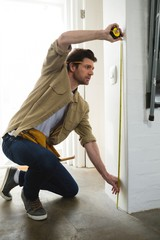 Male carpenter measuring a wall
