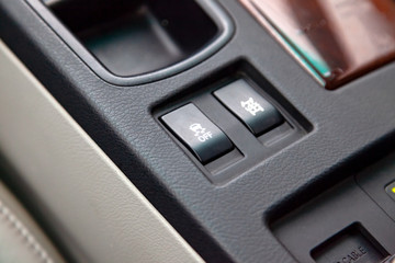 The buttons of the course control system are black and with white signs close-up in the interior of the car on the control console are gray.