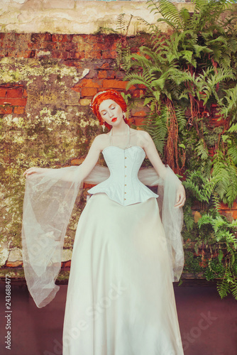 b8d4e250794 Renaissance redhead princess with hairstyle in corset. Renaissance queen  with magic hairdo against stone wall