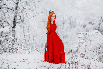 Beautiful snow maiden girl with red hair on fascinating nature. Beautiful redhead retro woman in red gown and with long gloves on background of fascinating winter nature. Snowfall in winter