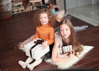 two little sisters with gift boxes, sitting on the floor in a cozy living room.