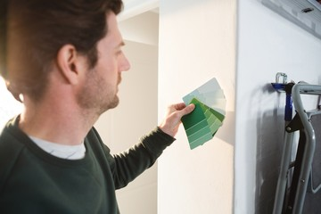 Male carpenter checking colour shade of wall