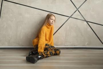pensive cute girl sitting near the wall.