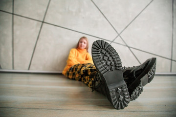 stylized photo of a girl in a yellow sweater sitting near the wall