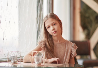 cute girl sitting at a table in a cafe
