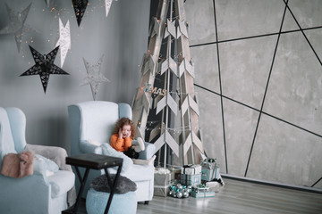 little girl sitting in the living room near a stylized Christmas tree.