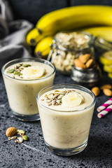 Oats banana almond milk shake with nuts and seeds on dark background. Selective focus, space for text.