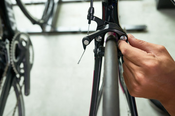 Close-up image of man checking every part of bicycle where to sell it
