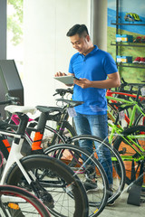 Smiling customer reading reviews on tablet computer before buying a bike