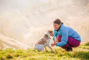 woman playing with her dog in beautiful mountain scenery in spring