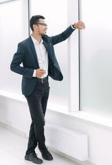 Executive businessman looking through a big office window