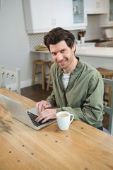 Man using laptop in kitchen at home