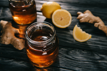 selective focus of  tea in glass jar on wooden table with ginger roots and lemons