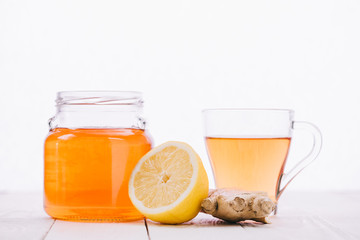 tea with lemon and ginger root in jar and glass cup on wooden table isolated on white