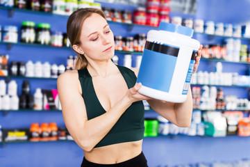 Woman choosing sport nutrition in shop