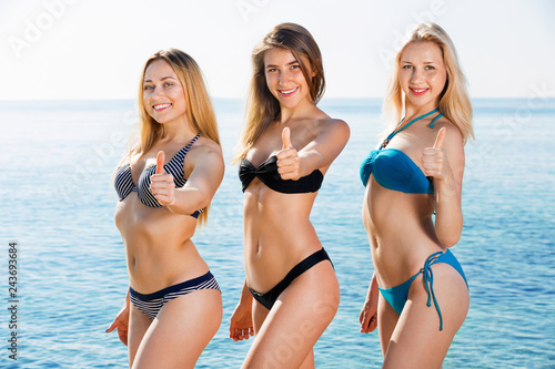 66cdee9704b Portrait of three cheerful young women on beach