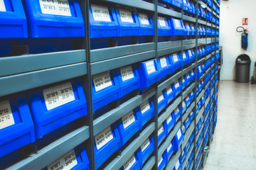 Blue plastic draws of stock / parts in rows of shelves in a warehouse