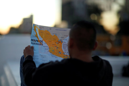 Man holds a map as he waits to leave with a new caravan of migrants, set to head to the United States, at El Salvador del Mundo Square in San Salvador