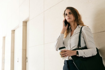 Serious businesswoman with cup of take away coffee talking on phone with coworker or business partner