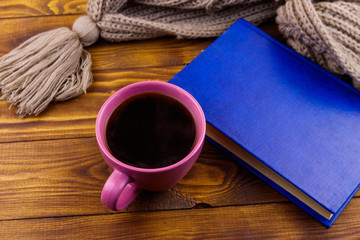 Cup of coffee, knitted scarf and book on wooden background