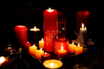 Several burning candles in the dark light