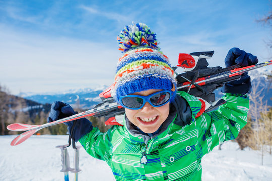 Cute skier boy in a winter ski resort.