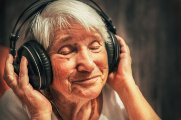 old woman in headphones listening to music