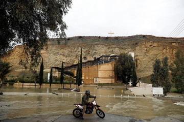 A motocross rider stands next to a flooded river, after heavy rainfall, by the Panagia Chrisospiliotissa church in the village of Deftera