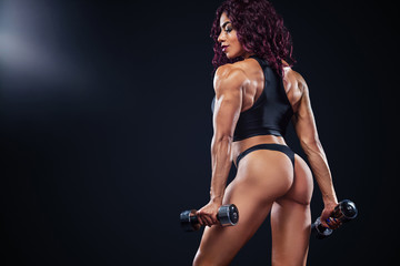 Sporty fit woman, athlete, egyptian and muslim with dumbbells makes fitness exercising on black background with lights.