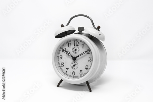 old white analog twin bell alarm clock isolated on a white