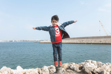 a Little boy stand up and open his hands like a bird and plane to flying with sea on background