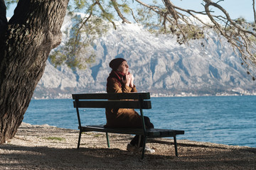 Woman in a beige coat listens to music or a podcast  by the sea. Snow-capped mountains on the background in Montenegro