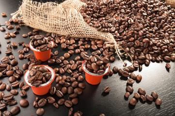 capsule with grain coffee on dark