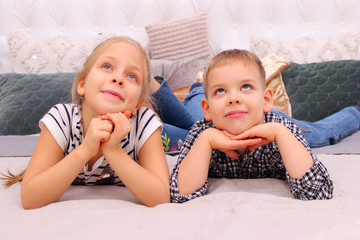People, Happiness, Friendly Family, Children, Family Value Concept. Brother And Sister Playing. Boy And Girl Lying On A Bed. Elder Sister And Her Younger Brother Dreaming.