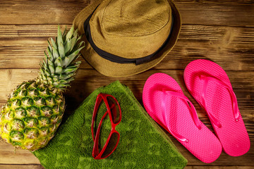 Summer holiday concept. Pineapple, straw hat, flip flops, towel and sunglasses on wooden background