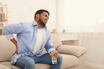 Young black man with back pain at home