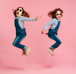 Twin sisters jumping in fashion outfits