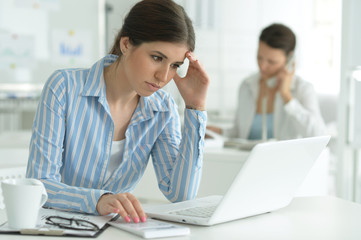Portrait of young attractive woman working with laptop in office