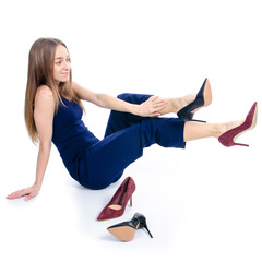Woman sits chooses high heel shoes on white background. Isolation