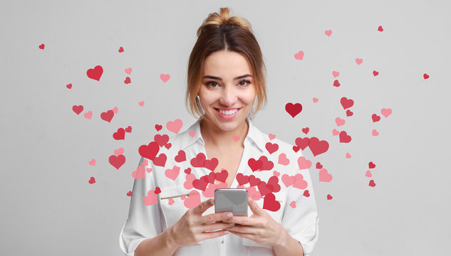 Love message for Valentine day - hearts flying out smartphone in girls hands